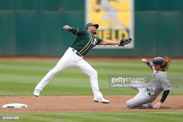 Ben Gamel of the Seattle Mariners steals second base as Marcus Semien of the Oakland Athletics fils to catch a ball thrown by catcher Bruce Maxwell...