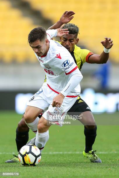 Ben Garuccio of Adelaide United beats the challenge of Roy Krishna of the Phoenix during the round one ALeague match between Wellington Phoenix and...