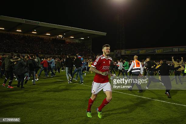 Ben Gladwin of Swindon Town runs off the pitch as fans invade at the final whistle during the Sky Bet League 1 Playoff SemiFinal between Swindon Town...