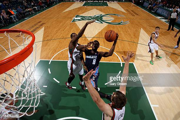 Ben Gordon of the Charlotte Bobcats shoots against Khris Middleton and Olek Czyz of the Milwaukee Bucks during the NBA Preseason game on October 12...