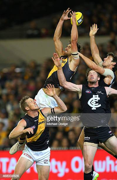 Ben Griffiths of the Tigers leaps for a high mark attempt over teamate Jack Riewoldt and Sam Rowe and Michael Jamison of the Blues during the round...