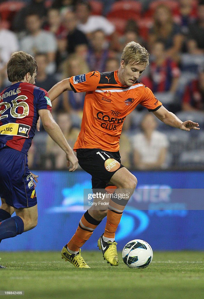 Ben Halloran of the Roar runs the ball past Andrew Hoole of te Jets during the round 16 A-League match between the Newcastle Jets and the Brisbane Roar at Hunter Stadium on January 12, 2013 in Newcastle, Australia.