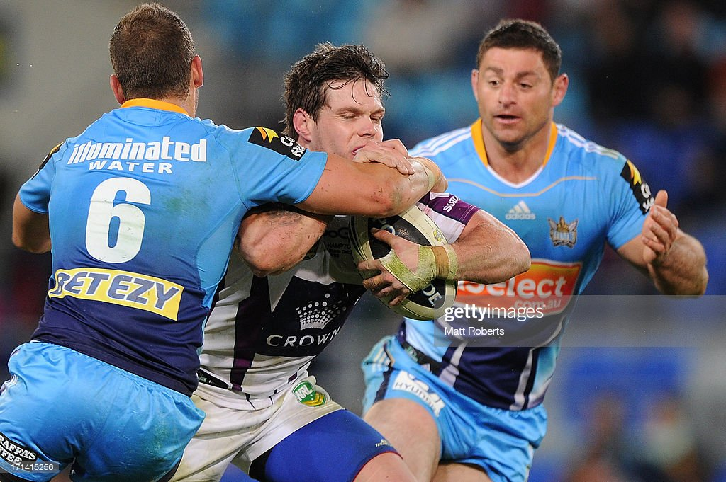 Ben Hampton of the Storm is tackled during the round 15 NRL match between the Gold Coast Titans and the Melbourne Storm at Skilled Park on June 24, 2013 on the Gold Coast, Australia.