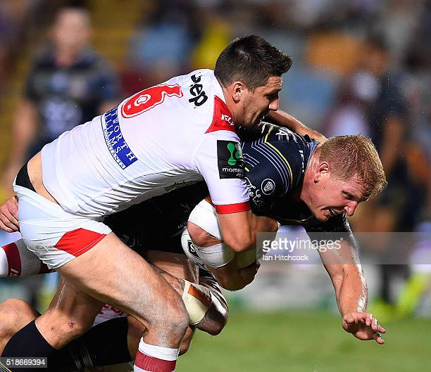 Ben Hannant of the Cowboys is tackled by Gareth Widdop of the Dragons during the round five NRL match between the North Queensland Cowboys and the St...