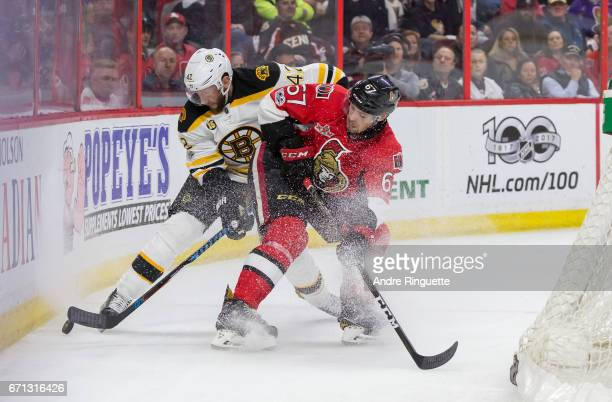 Ben Harpur of the Ottawa Senators defends against David Backes of the Boston Bruins in battle for the puck behind the net in Game Five of the Eastern...