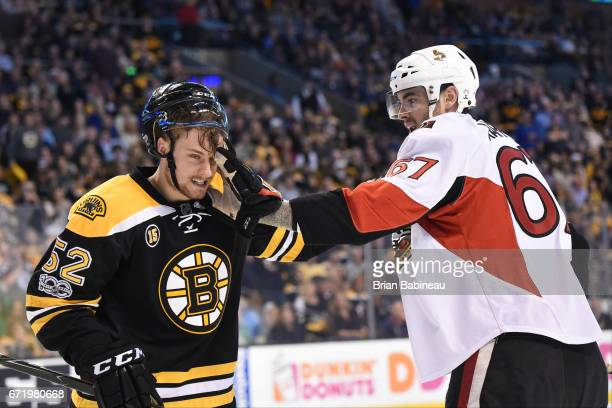 Ben Harpur of the Ottawa Senators pushes his glove into the face of Sean Kurlay of the Boston Bruins in Game Six of the Eastern Conference First...