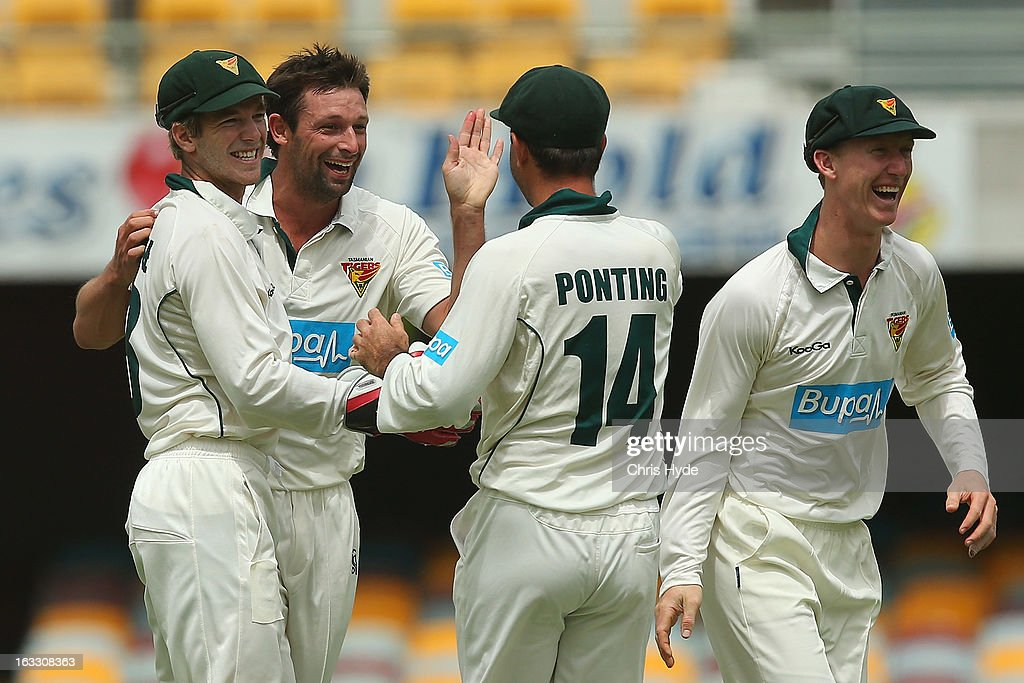 Ben Hilfenhaus of the Tigers celebrates with team mates after dismissing Dom Michael of the Bulls for a duck during day two of the Sheffield Shield match between the Queensland Bulls and the Tasmanian Tigers at The Gabba on March 8, 2013 in Brisbane, Australia.