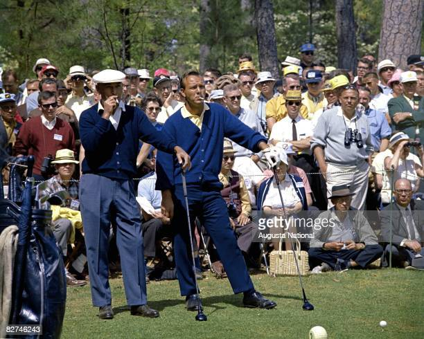 Ben Hogan and Arnold Palmer smoke as they wait in front of a gallery to play their tee shot on the second hole during the 1966 Masters Tournament at...