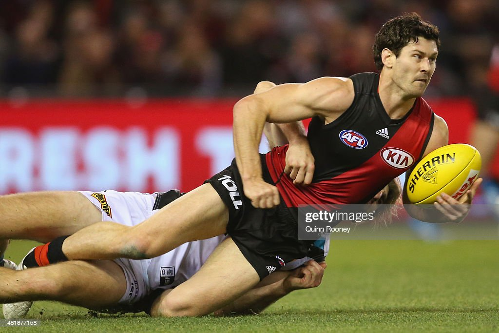 Ben Howlett of the Bombers handballs whilst being tackled by Justin Westhoff of the Power during the round 17 AFL match between the Essendon Bombers and the Port Adelaide Power at Etihad Stadium on July 25, 2015 in Melbourne, Australia.