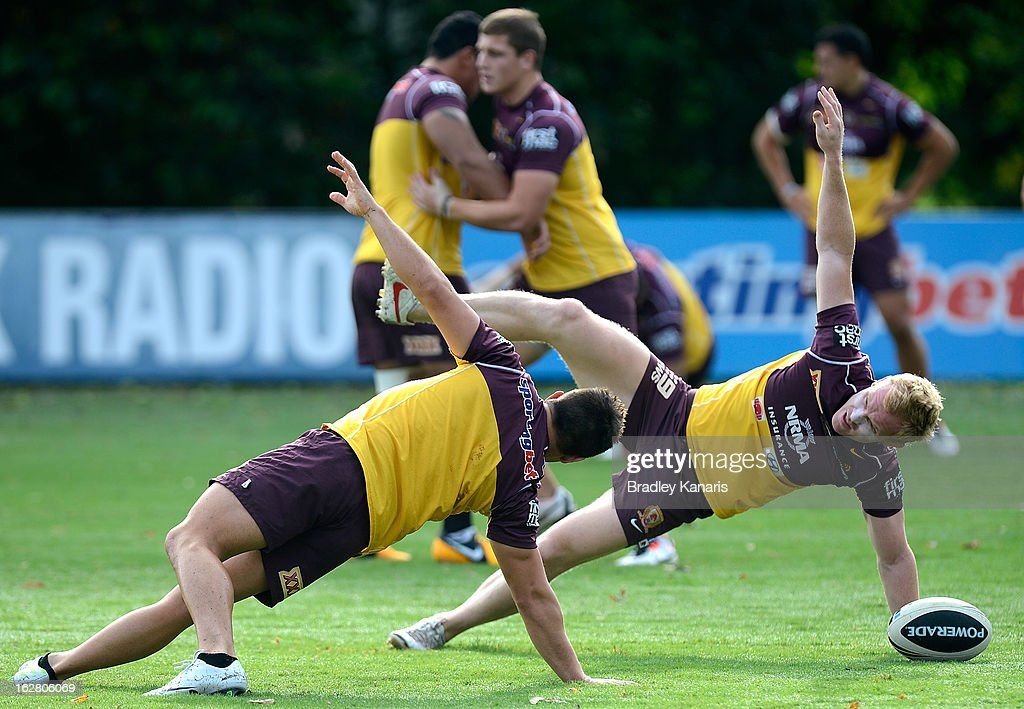 Ben Hunt (L) and Peter Wallace stretch during a Brisbane Broncos NRL training session on February 28, 2013 in Brisbane, Australia.