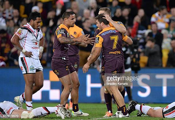 Ben Hunt of the Broncos celebrates with team mates after scoring a try during the round 19 NRL match between the Brisbane Broncos and the New Zealand...
