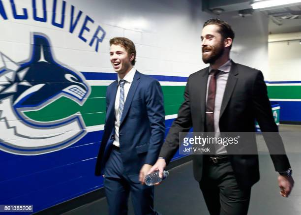 Ben Hutton and Erik Gudbranson of the Vancouver Canucks walk to their dressing room before their NHL game against the Calgary Flames at Rogers Arena...