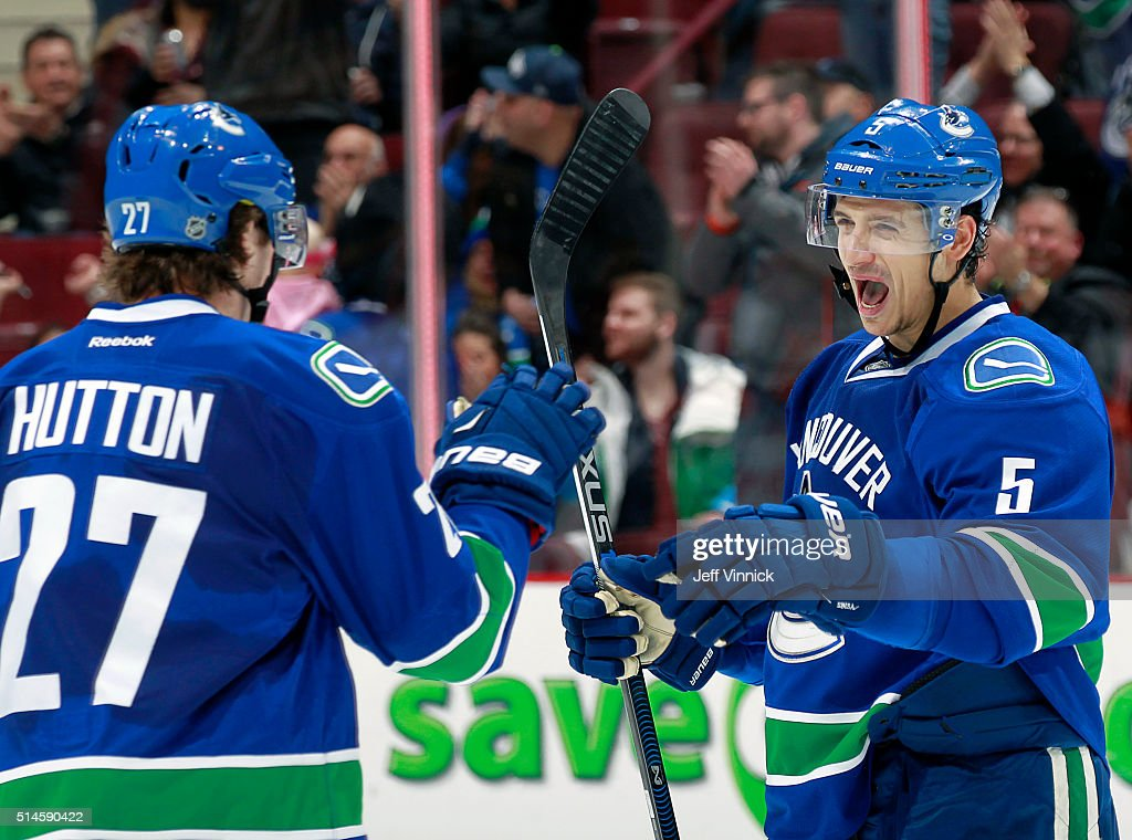 Ben Hutton congratulates Luca Sbisa of the Vancouver Canucks who scored against the Arizona Coyotes during their NHL game at Rogers Arena March 9...