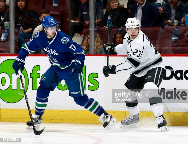 Ben Hutton of the Vancouver Canucks and Dustin Brown of the Los Angeles Kings skate up ice during their NHL game at Rogers Arena March 31 2017 in...