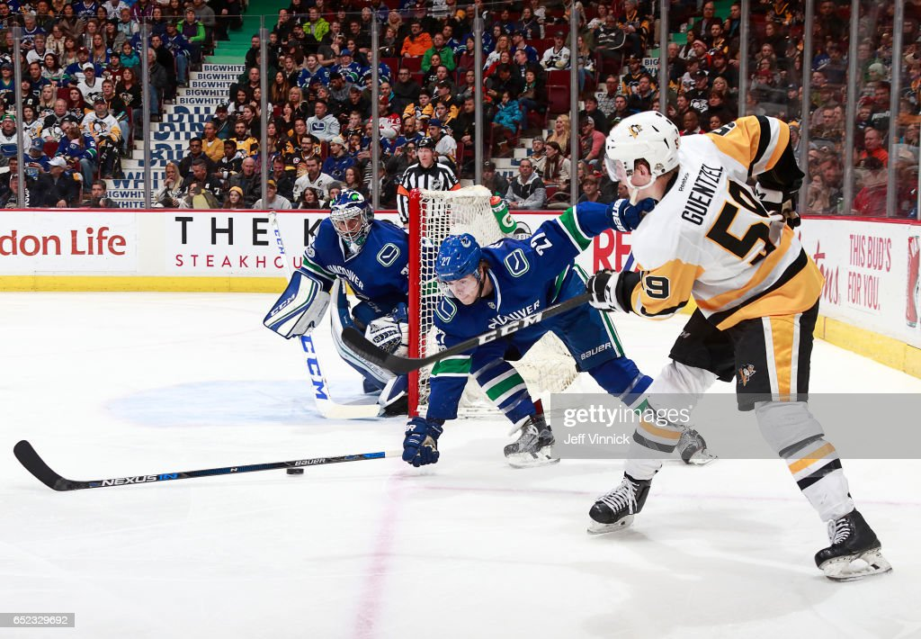 Ben Hutton #27 of the Vancouver Canucks blocks a shot from Jake Guentzel #59 of the Pittsburgh Penguins during their NHL game at Rogers Arena March 9, 2017 in Vancouver, British Columbia, Canada.