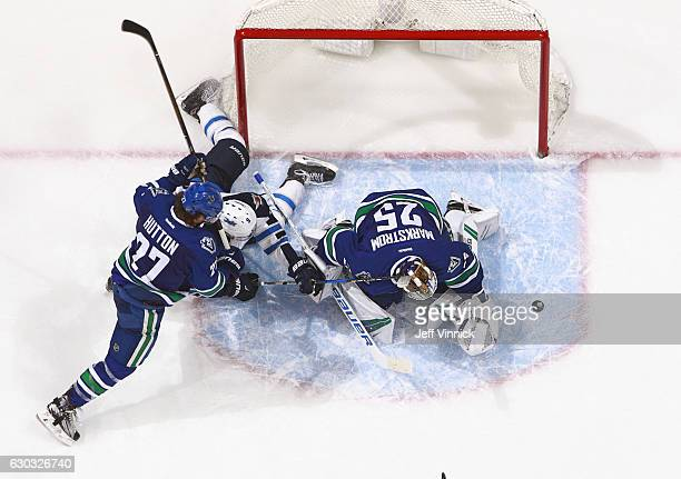 Ben Hutton of the Vancouver Canucks checks Andrew Copp of the Winnipeg Jets as Jacob Markstrom of the Vancouver Canucks redirects the puck during...