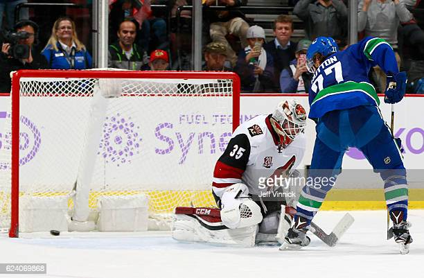 Ben Hutton of the Vancouver Canucks scores on Louis Domingue of the Arizona Coyotes on an overtime penalty shot during their NHL game at Rogers Arena...