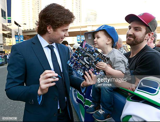 Ben Hutton of the Vancouver Canucks signs an autograph for young Hudson Reddemann as he arrives at Rogers Arena before their NHL game against the...