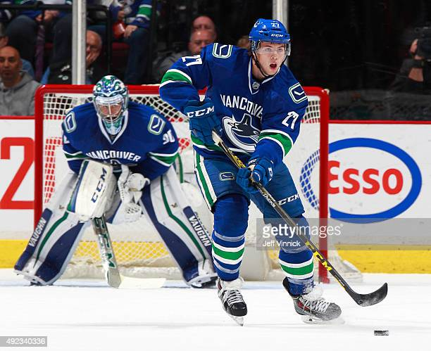 Ben Hutton of the Vancouver Canucks skates up ice with the puck during their NHL game against the Calgary Flames at Rogers Arena October 10 2015 in...