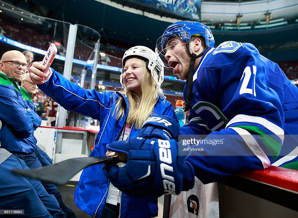 Ben Hutton #27 of the Vancouver Canucks takes a photo with a fan before his NHL game against the Calgary Flames at Rogers Arena January 6, 2017 in Vancouver, British Columbia, Canada. Vancouver won 4-2.