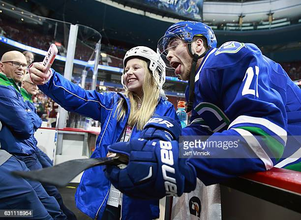 Ben Hutton of the Vancouver Canucks takes a photo with a fan before his NHL game against the Calgary Flames at Rogers Arena January 6 2017 in...