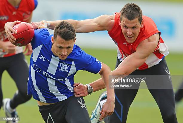 Ben Jacobs is tackled by Daniel Currie during a North Melbourne Kangaroos AFL training session at Arden Street Ground on August 14 2014 in Melbourne...