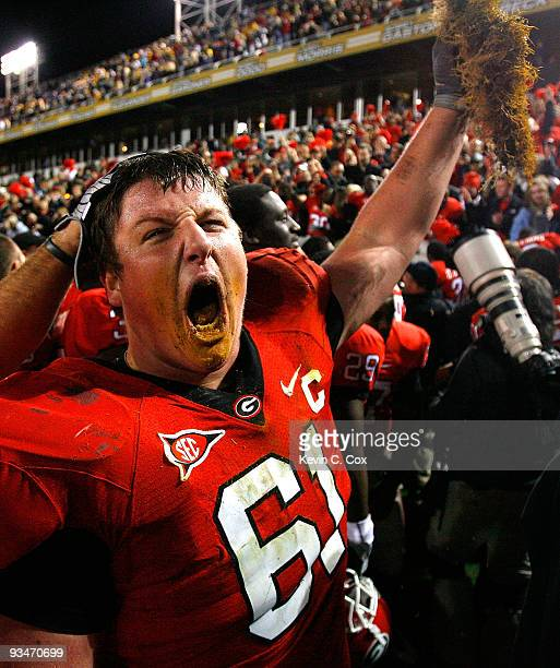 Ben Jones of the Georgia Bulldogs celebrates their 3024 win over the Georgia Tech Yellow Jackets with a some grass from the end zone at Bobby Dodd...