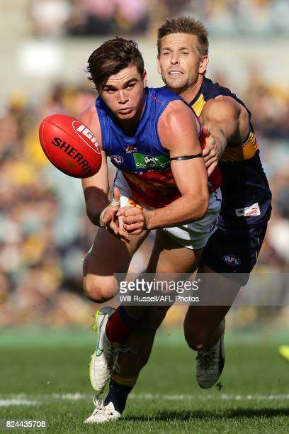 Ben Keays of the Lions handpasses the ball under pressure from Mark LeCras of the Eagles during the round 19 AFL match between the West Coast Eagles...