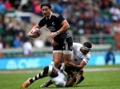 Ben Lam of New Zealand is tackled by Viliame Mata and Donasio Ratubuli of Fiji during the Marriot London Sevens match between New Zealand and Fiji at...