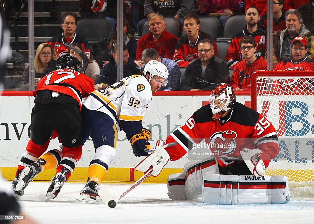 Ben Lovejoy #12 and Cory Schneider #35 of the New Jersey Devils defend against Ryan Johansen #92 of the Nashville Predators during the first period at the Prudential Center on December 20, 2016 in Newark, New Jersey.