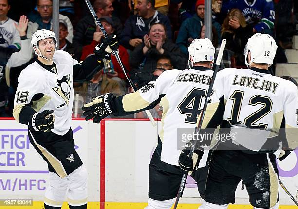 Ben Lovejoy and Rob Scuderi congratulate Eric Fehr of the Pittsburgh Penguins who scored against the Vancouver Canucks during their NHL game at...