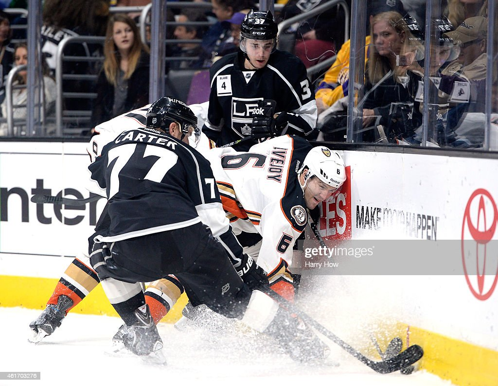 Ben Lovejoy #6 of the Anaheim Ducks attempts to clear the puck as Nick Shore #37 and Jeff Carter #77 of the Los Angeles Kings follow the puck during the second period at Staples Center on January 17, 2015 in Los Angeles, California.