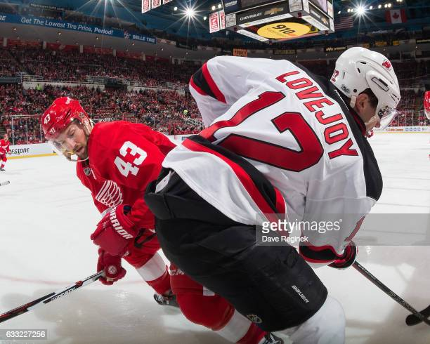 Ben Lovejoy of the New Jersey Devils battles along the boards with Darren Helm of the Detroit Red Wings during an NHL game at Joe Louis Arena on...
