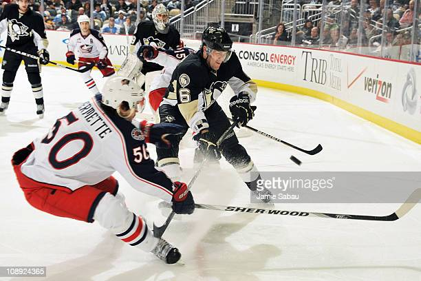 Ben Lovejoy of the Pittsburgh Penguins and Antoine Vermette of the Columbus Blue Jackets battle for control of the puck in the second period on...