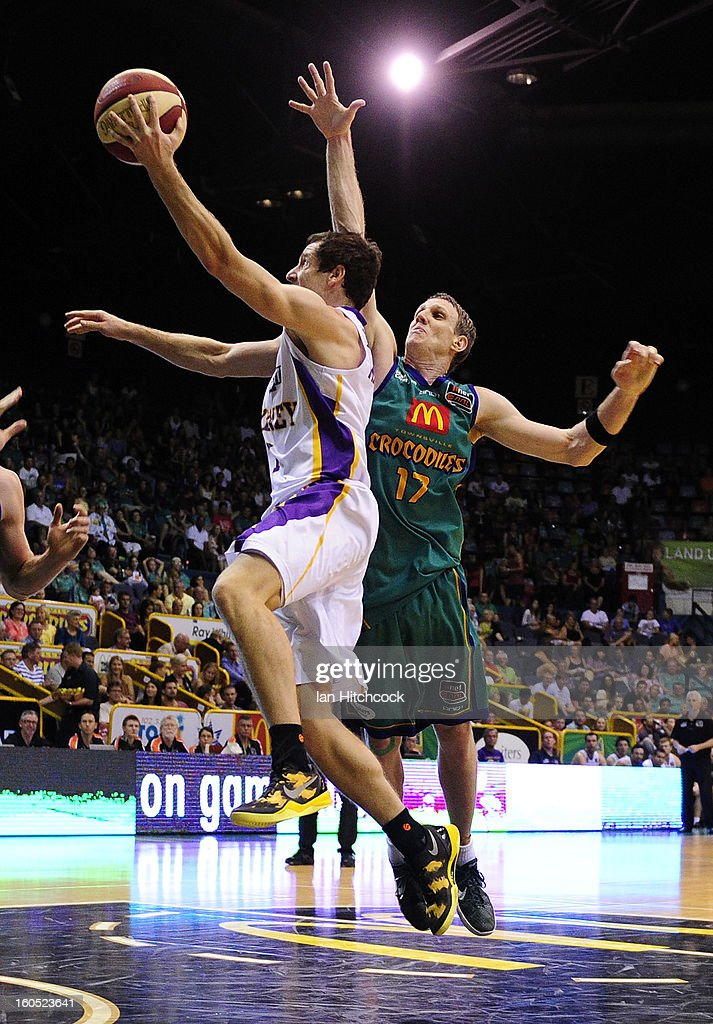 Ben Madgen of the Kings attempts a layup past Peter Crawford of the Crocodiles during the round 17 NBL match between the Townsville Crodcodiles and the Sydney Kings at Townsville Entertainment Centre on February 2, 2013 in Townsville, Australia.