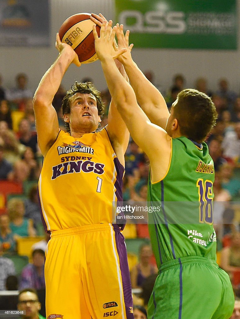 Ben Madgen of the Kings takes a jump shot over Mirko Djeric of the Crocodiles during the round 15 NBL match between the Townsville Crocodiles and Sydney Kings at Townsville RSL Stadium on January 16, 2015 in Townsville, Australia.