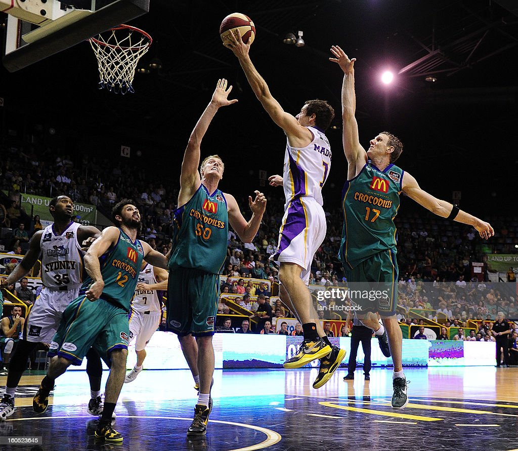 Ben Madgen of the Kings takes a shot past Luke Nevill and Peter Crawford of the Crocdiles during the round 17 NBL match between the Townsville Crodcodiles and the Sydney Kings at Townsville Entertainment Centre on February 2, 2013 in Townsville, Australia.