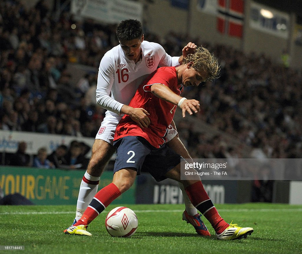 Ben Marshall of England and Vega Hedenstad (R) of Norway compete for the ball during the UEFA Under 21 Championship match between England and Norway at the B2NET Stadium on September 10, 2012 in Chesterfield, England