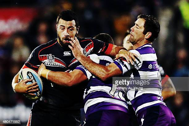 Ben Matulino of the Warriors charges into Cameron Smith and Kenny Bromwich of the Storm during the round 18 NRL match between the New Zealand...