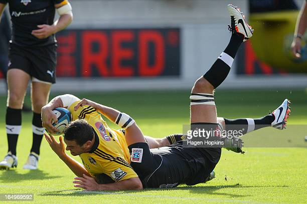 Ben May of the Hurricanes beats the tackle of Wimpie van der Walt of the Kings to score a try during the round seven Super Rugby match between the...