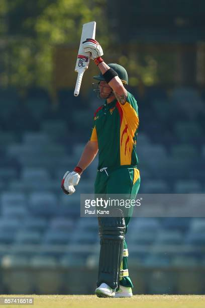 Ben McDermott of the Tigers raises his bat to the rooms after reaching his half century during the JLT One Day Cup match between Victoria and...