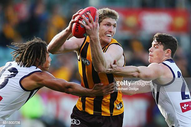 Ben McEvoy of the Hawks looks upfield from Tendai Mzungu of the Dockers and Lachie Neale during the round eight AFL match between the Hawthorn Hawks...