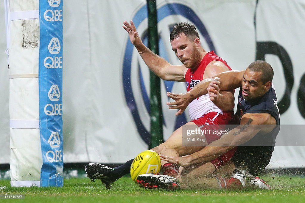 Ben McGlynn of the Swans gets his foot on the ball to kick a goal despite the defence of Chris Yarran of the Blues during the round 14 AFL match between the Sydney Swans and the Carlton Blues at SCG on June 28, 2013 in Sydney, Australia.
