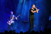 Ben McKee and Dan Reynolds of Imagine Dragons perform at Deck the Hall Ball at Key Arena on December 9 2014 in Seattle Washington