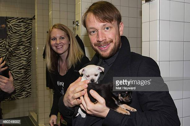 Ben McKee of Imagine Dragons holds two puppies brought by Motley Zoo Animal rescue backstage during Deck The Hall Ball hosted by 1077 The End at...