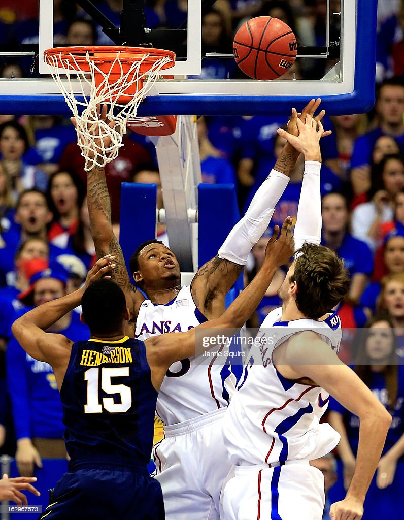 Ben McLemore #23 and Jeff Withey #5 of the Kansas Jayhawks block a shot by Terry Henderson #15 of the West Virginia Mountaineers during the game at Allen Fieldhouse on March 2, 2013 in Lawrence, Kansas.