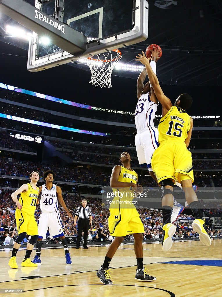 Ben McLemore of the Kansas Jayhawks dunks over Glenn Robinson III and Jon Horford of the Michigan Wolverines in the first half during the South...