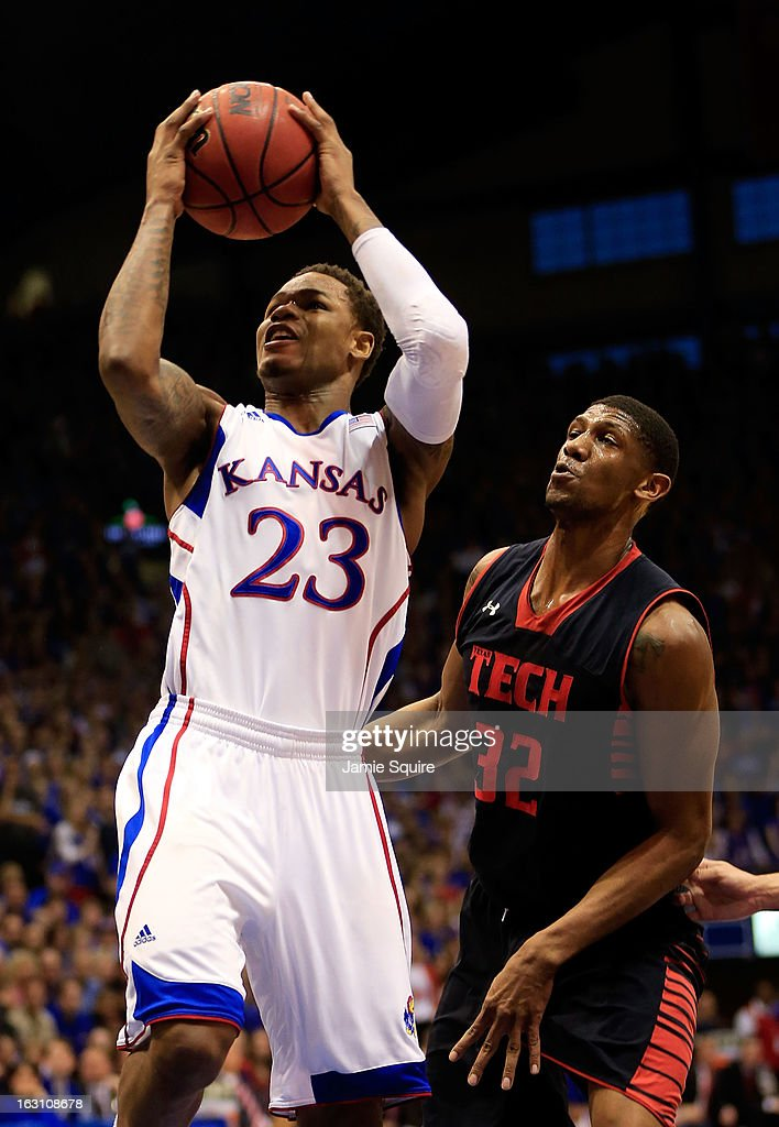 Ben McLemore #23 of the Kansas Jayhawks shoots as Jordan Tolbert #32 of the Texas Tech Red Raiders defends during the game at Allen Fieldhouse on March 4, 2013 in Lawrence, Kansas.