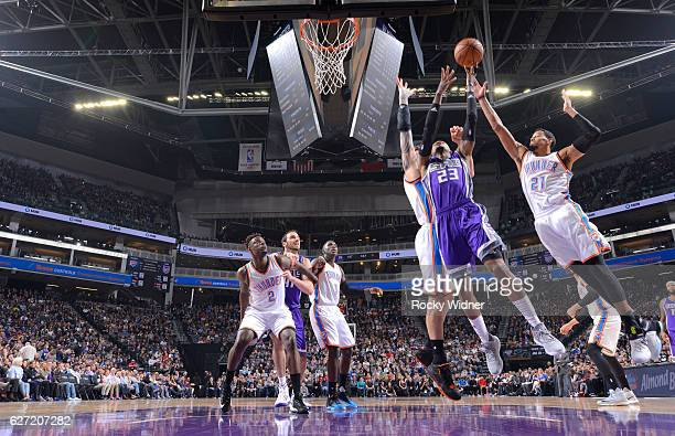 Ben McLemore of the Sacramento Kings goes up for the shot against Steven Adams and Andre Roberson of the Oklahoma City Thunder on November 23 2016 at...