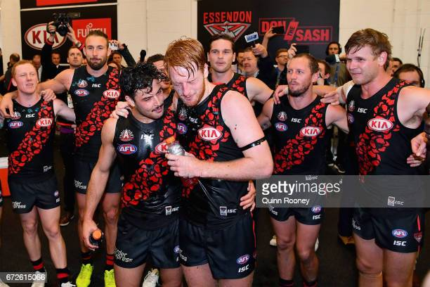 Ben McNiece and Aaron Francis of the Bombers are sprayed with drinks as they sing the song in the rooms after winning the round five AFL match...
